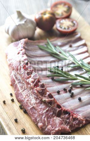 Raw lamb ribs with fresh rosemary on the wooden board