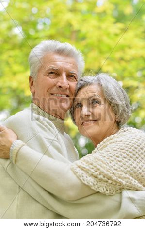 portrait of beautiful caucasian senior couple  in the park looking away