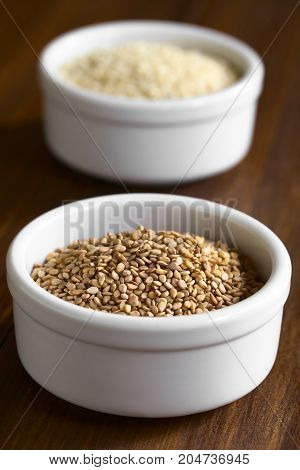Roasted and white sesame seeds in small bowls photographed with natural light (Selective Focus Focus one third into the roasted seeds)