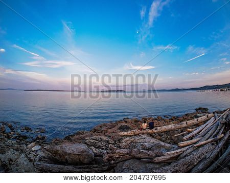 Young couple enjoying sunset view at the shore in Sidney Vancouver Island British Columbia Canada