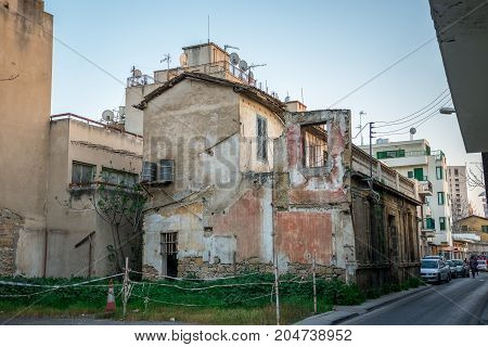 Nicosia, Cyprus, March 2017: A house with broken walls and outside water barrels for water supply in Nicosia city centre Cyprus