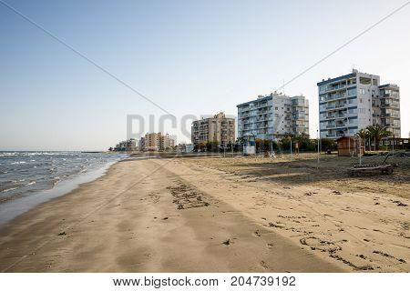 Larnaca, Cyprus, March 2017: Empty off season Kastela beach in Larnaca with residential apartment blocks Cyprus