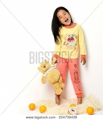 Happy asian korean girl with teddy bear standing yelling and looking at the camera isolated on white background
