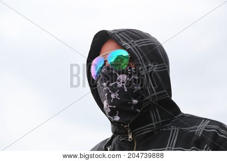 Young man Hooligan in bandana with skulls
