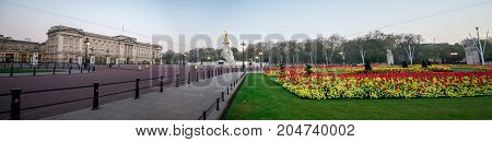 London, England, April 2017: Square panorama with Queen Victoria memorial and flower-beds in front of Buckingam Palace London England