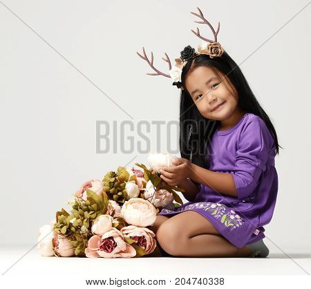Happy young little child girl kid with bouquet of flowers and deer rim on grey background