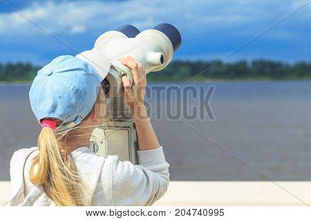 girl looking through binoculars at the pier