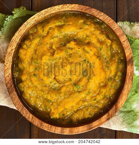 Pumpkin and parsley puree in wooden bowl photographed overhead on dark wood with natural light (Selective Focus Focus on the puree)