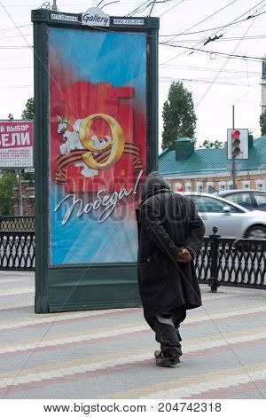 Voronezh, Russia - Circa 2014: Homeless old man on background of banner May 9 Victory Day