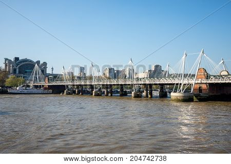 London, England, April 2017: A view of Golden Jubilee and Hungerford bridges from South Bank of Thames River in London England