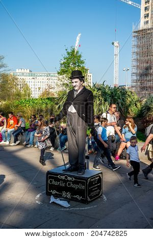 London, England, April 2017: One of the street performers dressed up as Charlie Chaplin near Jubilee gardens and London Eye Observation Wheel England