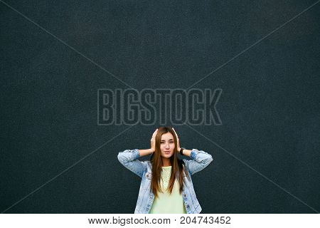 The girl closes her ears on a dark background, a lot of free space for an inscription, a brunette
