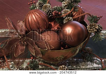 horizontal Christmas display of a brass bowl filled with red ball ornaments, pine cones, and a poinsettia flower