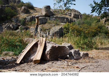 Friends prepared firewood for the fire. A beautiful view of nature against the background of a fire. Summer travels to nature. A great pastime in the summer. The knife sticks out in a piece of wood.