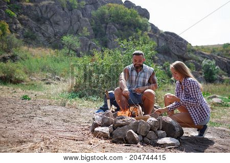 A sweet girl helps her boyfriend to kindle a fire on the nature. A young couple is preparing to grill meat on the grill. Healthy lifestyle. Organizing the camp fire for barbeque, helping each other.