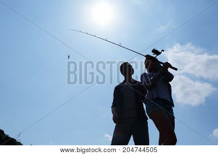 A young couple went on a trip with a fishing rod and takes a fish in a mountain river