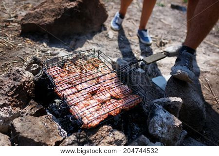 A young couple is traveling in the mountains. Summer journey of lovers, a guy frying meat at a bonfire for a girl. Healthy way of life, travel, summer vacation. The best pastime in the summer.
