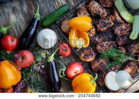 High Angle View of Grilled Meal of Steak, Chicken and Vegetables Spread Out on Rustic Wooden Table at Barbeque Party. Grilled meat and vegetables on rustic wooden table. Summer picnic time.