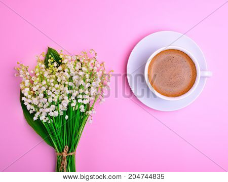 a cup of black coffee and a blooming bouquet of lilies of the valley on a pink background top view