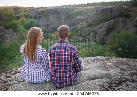 Couple's legs together on the rock on top of the hill with mountain ridge on the background. Hikers boots. Summer time, explore together. Summer hike in the mountains for a vacation. Beautiful view.