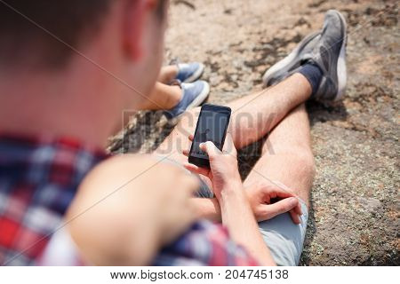 A young couple is resting sitting on a rock. The guy shows photos to his girlfriend. Summer trip to the canyon. adventure travel tourism hike and people concept. The best time to hike in the mountains