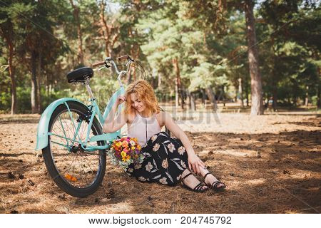 A beautiful young woman sits with flowers in the forest near her bicycle and enjoys the weather. Girl on nature. Spring flowers. Fashion beauty. Autumn forest in the sunny afternoon.