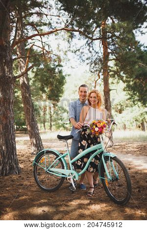Girl and guy with a bicycle in a pine forest on a sandy road. Happy woman with flowers. blue bicycle.