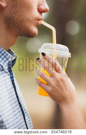 A man is drinking orange juice in a coniferous forest. Blurred Background
