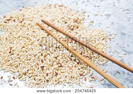 Yellow rice and wooden chopsticks on a metal plate
