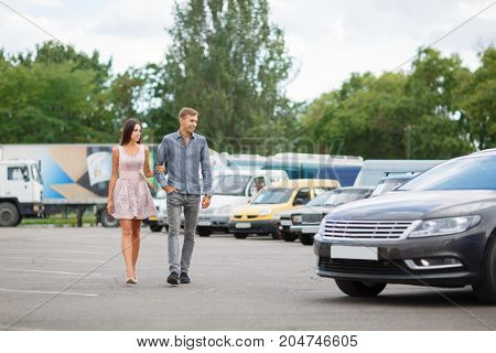 Beautiful young couple standing at the dealership choosing the car to buy. A beautiful sunny day to buy a new car. Happy beautiful couple is choosing a new car at dealership. Parking for sale.