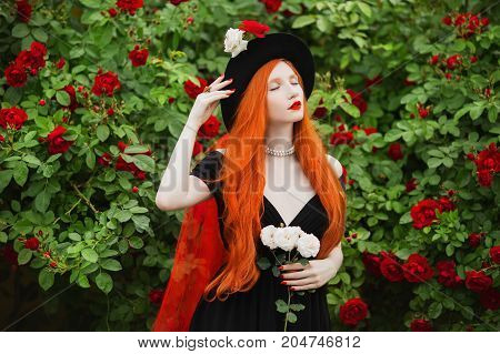 Redhead edwardian woman with very long hair with unusual appearance in black edwardian dress against background of red roses. Attractive edwardian girl with pale skin and bright appearance with black edwardian hat and red veil. Art photo. Edwardian model