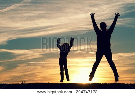 a mother with her child jumping at sunset.