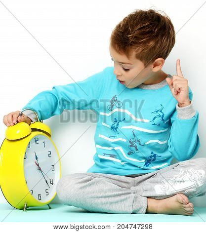 Happy young boy sitting in blue sweater thinking and looking up with big yellow clock pointing finger up on white background