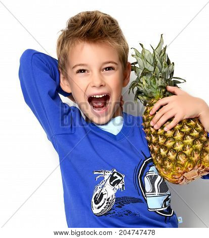 Happy young boy shouting laughing holding pineapple on white background