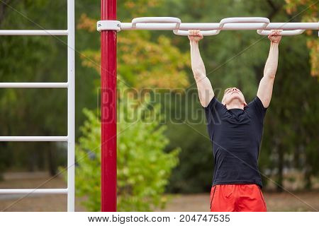 Closeup of strong athlete doing pull-up on horizontal bar. Mans fitness with blue sky in the background and open space around him.