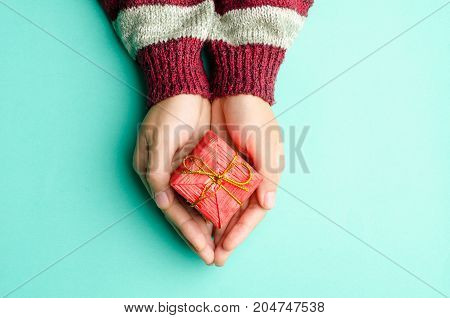 Woman holding red gift box by hand on green background for giving
