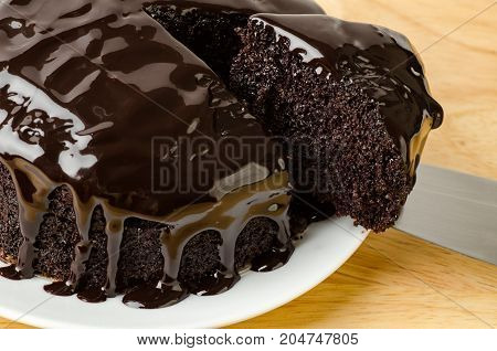 Hand hold knife and cutting of chocolate cake on white dish,piece of cake