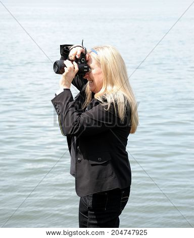 Mature female blond photographer on assignment outdoors.
