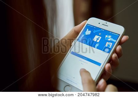 Bangkok Thailand - September 19, 2017 : hand is pressing the Facebook screen on apple iphone6 Social media are using for information sharing and networking.
