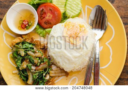 Thai food, spicy stir fried crispy chicken with basil and fried egg (Kapao kai Khai dao)
