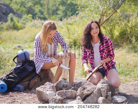 Friends are trying to set fire to burn meat. A summer trip of friends in the nature for a pleasant pastime. Vacations in the fresh air, away from city vanity. Healthy way of life, rest of friends.