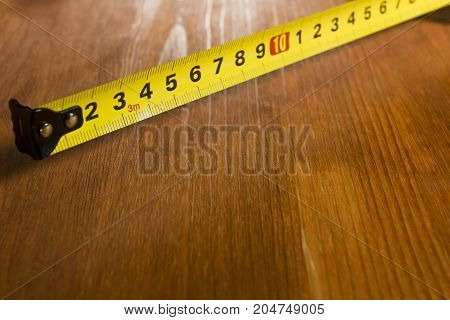 Part of the measuring tape on a wooden table