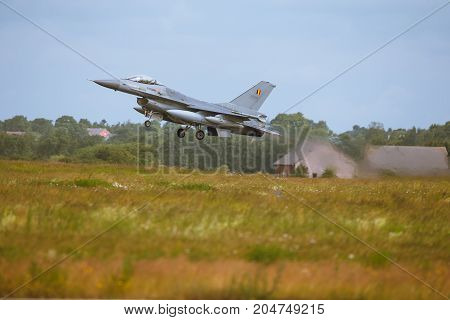 Schleswig - Jagel Germany - June 19 2014:Belgium - Air Force F-16 Fighting Falcon board number FA-109 is takeoff for background of field and skyline the airbase during NATO Tiger Meet 2014