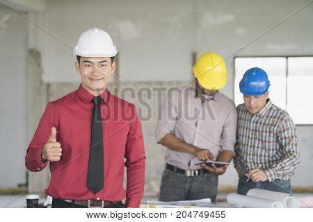 Asian engineers were consulted together and plan in construction site