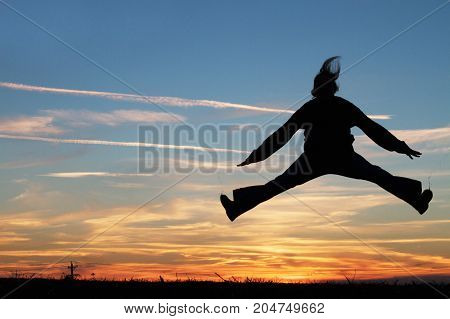 a woman jumping for joy at sunset.