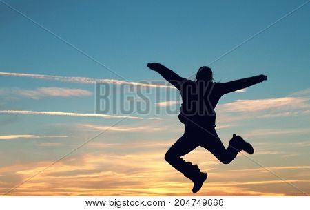a woman jumping in joy at sunset.