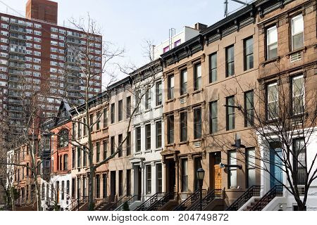 Row of historic brownstone buildings with colorful doors along a block in Manhattan New York City NYC