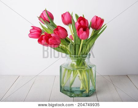 bunch of red tulip flowers in a glass vintage jar on rustic wooden table against white plaster wall