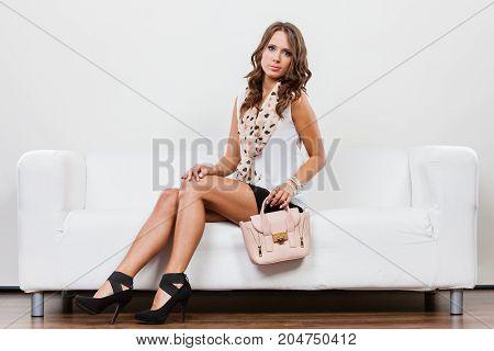 Elegant outfit. Female fashion. Girl in fashionable clothes sitting on sofa holding bag handbag.