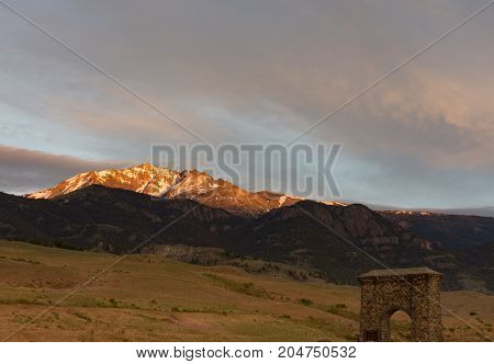 Electric Peak at Sunset with the foothills valley and Roosevelt Arch in the foreground.